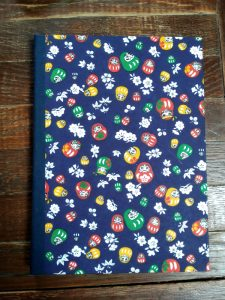 Notepad cover with dark blue Japanese washi paper depicting Daruma dolls